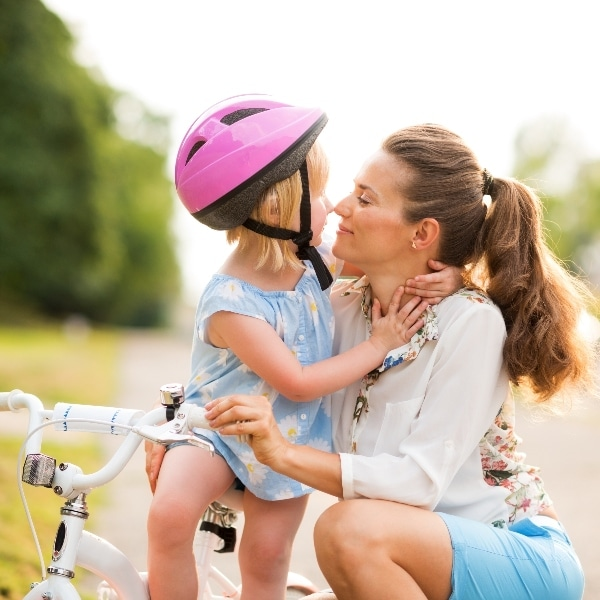 a mom hugging a little girl on a bike with trees in the background