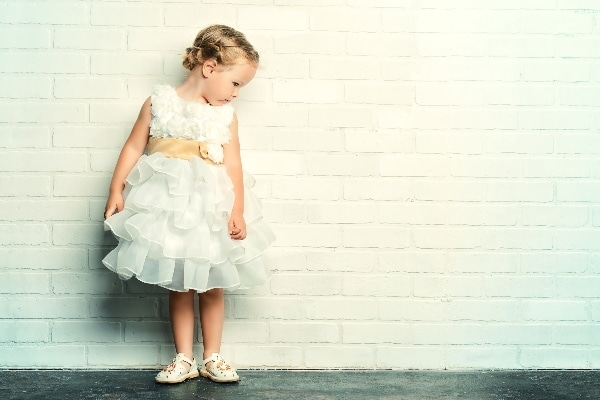 a little girl in a fancy standing with a white brick background