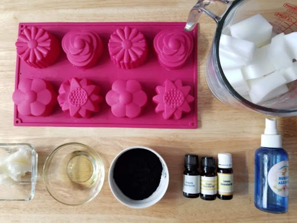 a soap mold tray, goat's milk soap base in a glass measuring cup, essential oil bottles, 3 small cups filled with charcoal and other soap making ingredients all on a brown table