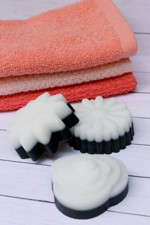 charcoal soap with peach colored towels in the background all on a white table