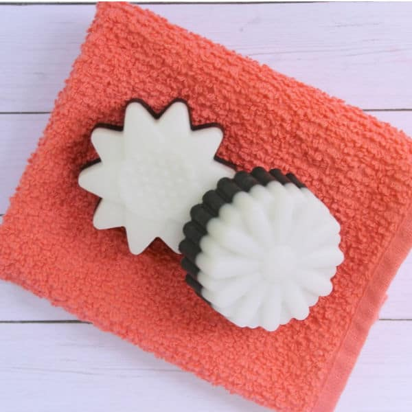 two charcoal soaps on an orange towel on a white table