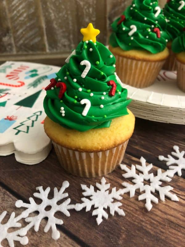 Cupcake with green frosting on top in the shape of a Christmas tree, with candy cane sprinkles and a star on top. More cupcakes and snowflakes are in the background.