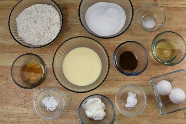 glass bowls of flour, sugar, baking soda, baking powder, salt, allspice. eggs, vegetable oil, spiced rum, eggnog, sour cream all on a brown table
