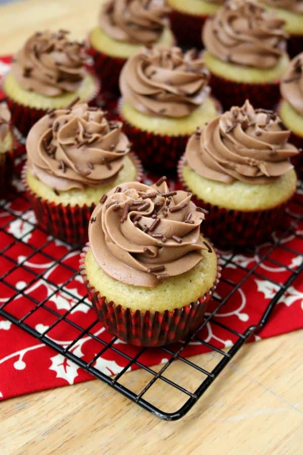 Eggnog cupcakes with chocolate frosting and chocolate sprinkles on a cooling rack on a red and white napkin.