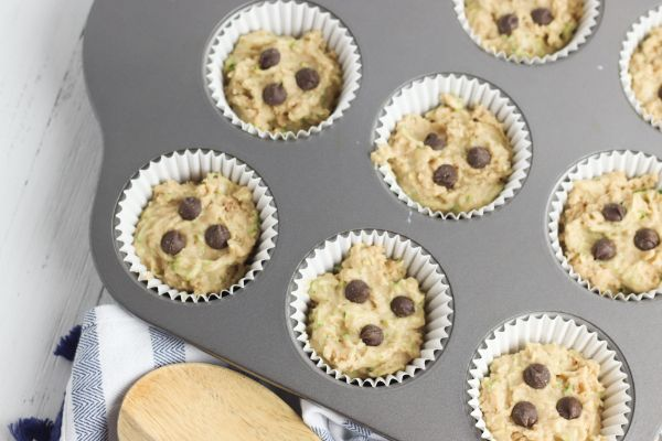 adding chocolate chips to the batter in muffin tin for healthy chocolate chip muffins