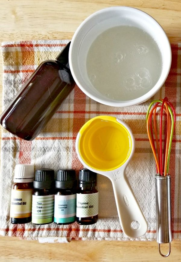 a white bowl of castille soap, bottles of essential oils, a measuring cup, small whisk on a linen to make homemade lice spray