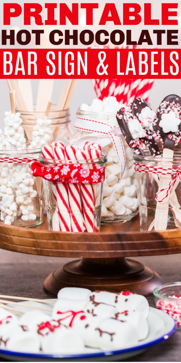 a wooden tray with glass jars filled with candy canes, marshmallows and chocolate spoons with title text reading Printable Hot Chocolate Bar Sign and Labels