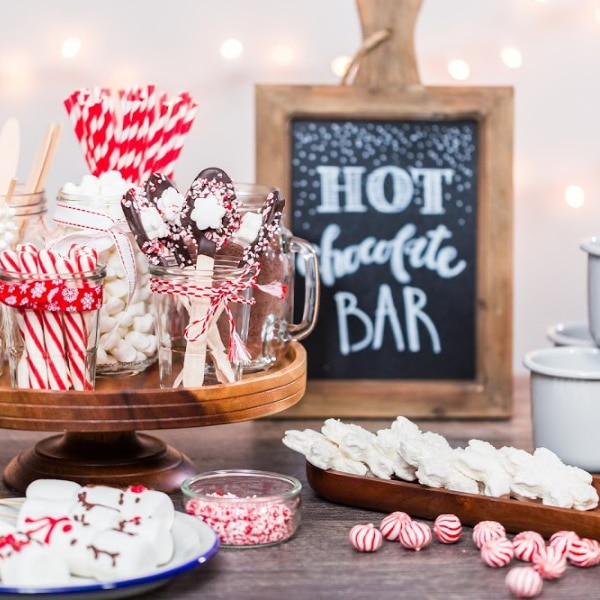 Hot Chocolate Bar sign, jars filled with candy canes, marshmallows, chocolate spoons and candy on plates on a table