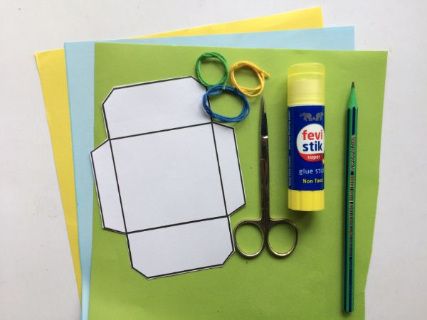 supplies needed for mini envelope template, including green, yellow and blue paper, scissors, glue stick and pencil on a white background