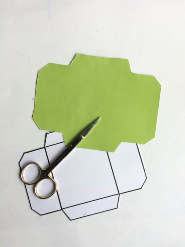 printable mini envelope template and green paper cut out in the shape, next to scissors on a white background