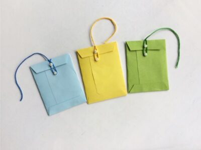 blue, yellow, green miniature envelopes with string closing the envelopes