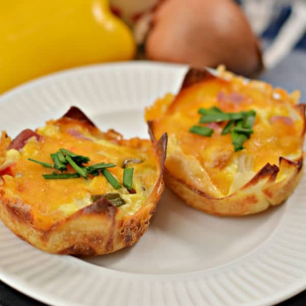 Muffin Tin Western Omelets on a white plate with a pepper, onion and cheese in the background