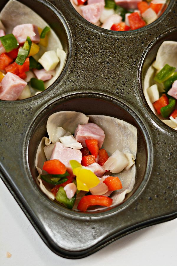 wonton wrappers, ham and veggies in a muffin tin