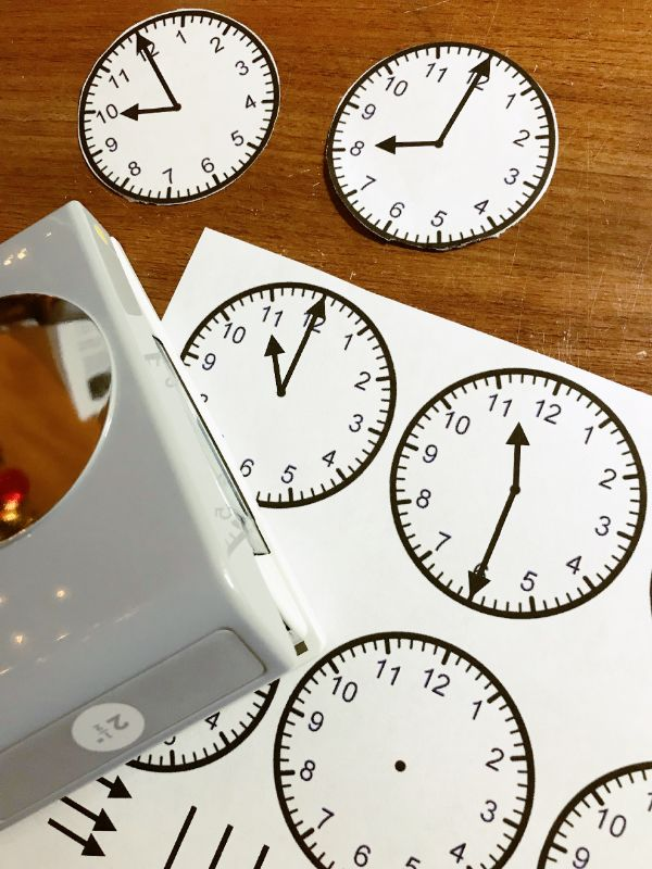 a circle punch with a paper printout of clock faces on a table