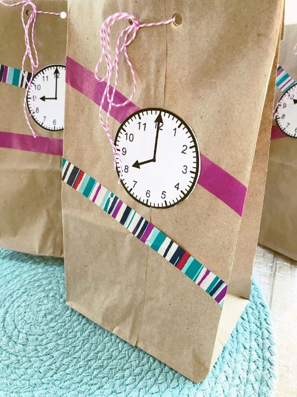 paper bags with paper clocks glued on them and ribbons on a green linen