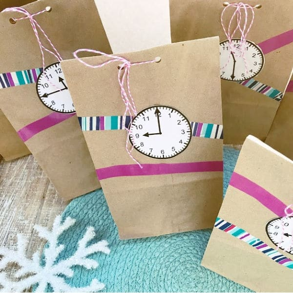 paper bags with paper clocks glued on them and ribbons with a snowflake in the background on a green linen