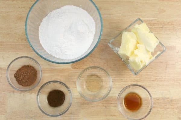 Six glass bowls with baking ingredients like flour, butter, vanilla and cinnamon.