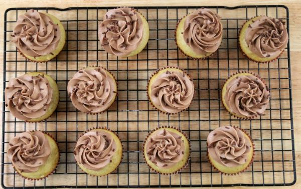 A wire rack with twelve eggnog cupcakes on it topped with chocolate frosting and chocolate sprinkles.