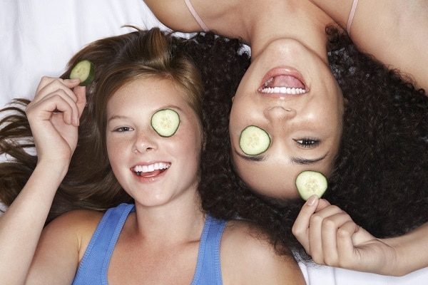 two girls laying down with a slice of cucumber on their eye and in their hand