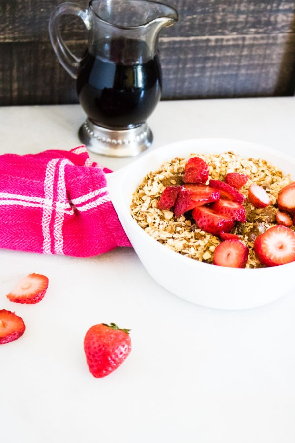 Amish Baked Oatmeal Topped with Strawberries in a white bowl on a white counter next to some strawberries, a red and white cloth and a glass jar of syrup