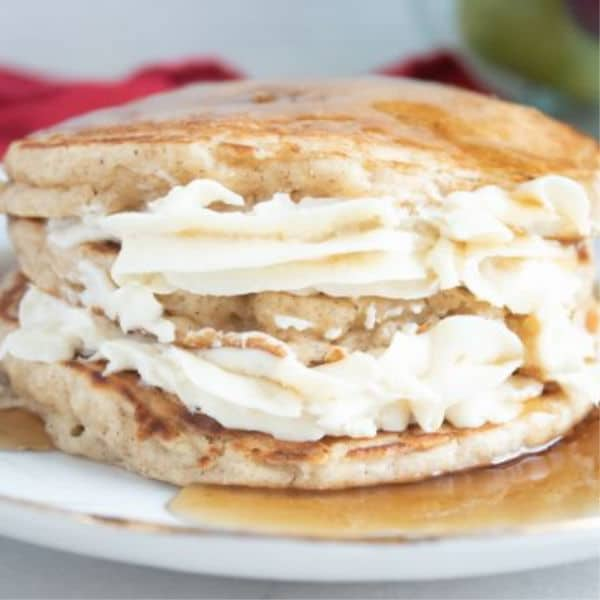 Apple Cheesecake Pancakes topped with syrup on a white plate