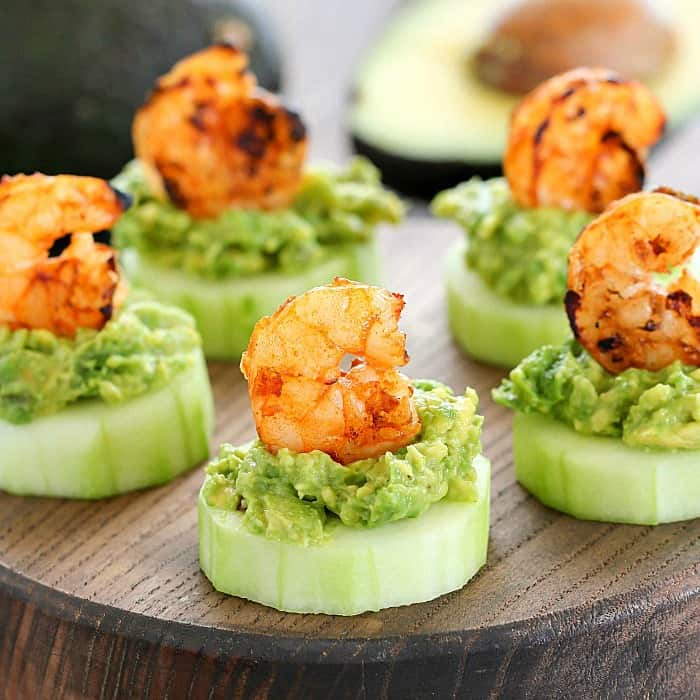 cucumbers topped with avocado and a shrimp on a wooden table
