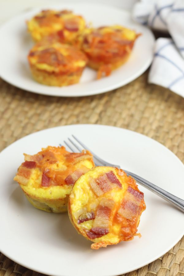 bacon and egg cups on a white plate with a fork on a brown mat with a cloth in the background and another plate of bacon and egg cups