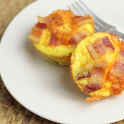 easy bacon and egg cups on a plate with a tan background