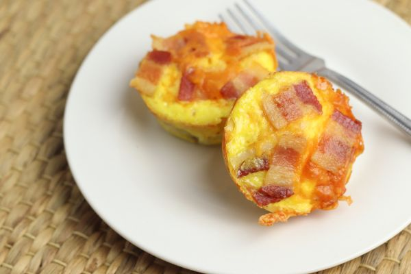 easy bacon and egg cups and a fork on a plate with a tan background