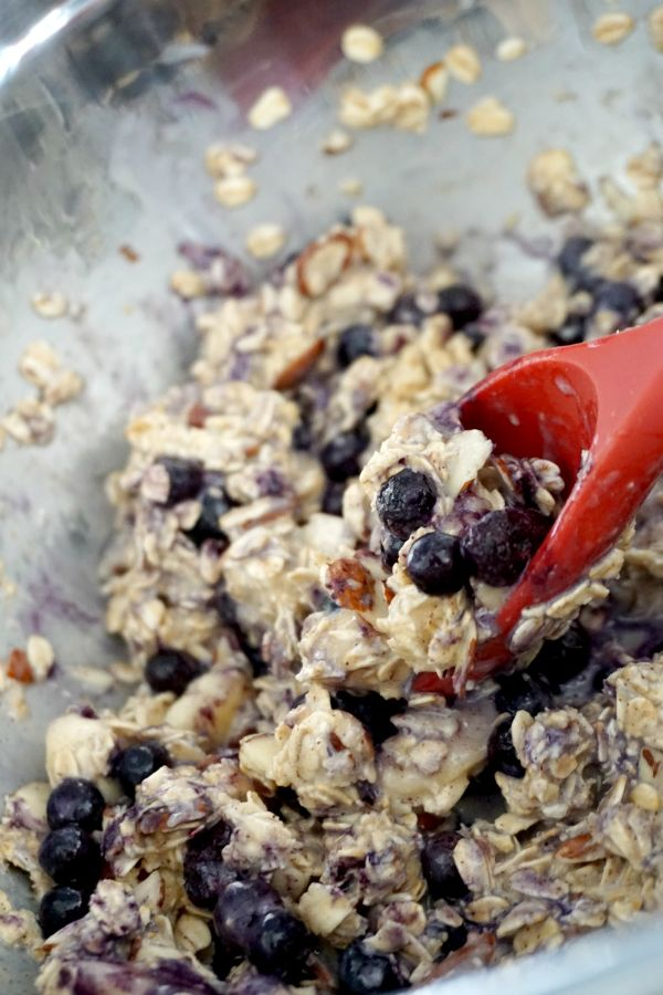 adding blueberries to blueberry almond baked oatmeal cups mixture in bowl