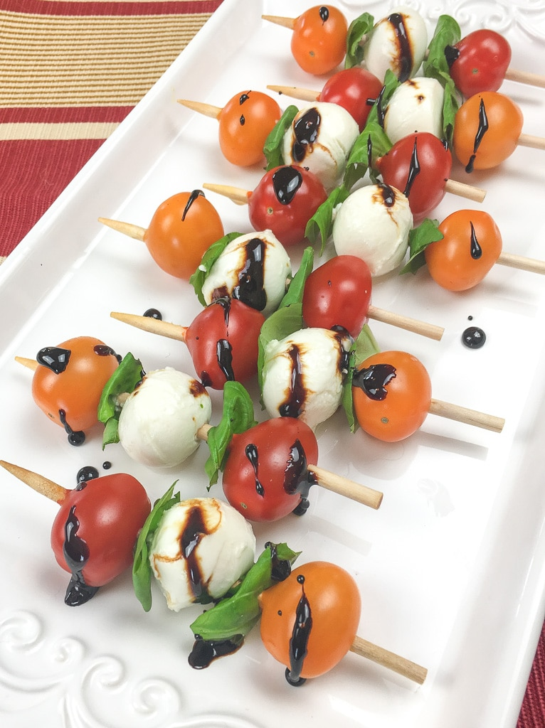 skewers with orange and red tomatoes, cheese balls and greens drizzed with balsamic vinegar on a white tray on a red and yellow linen