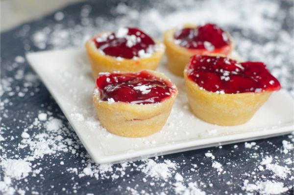 cherry pie filling in cookie cups sprinkled with powder sugar on a white plate on a gray counter with powder sugar on it