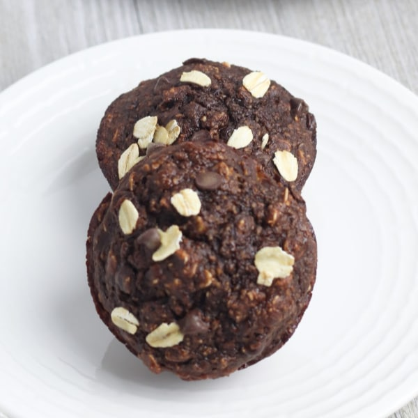 two Chocolate Banana Oat Chocolate Chip Muffins on a white plate on a table