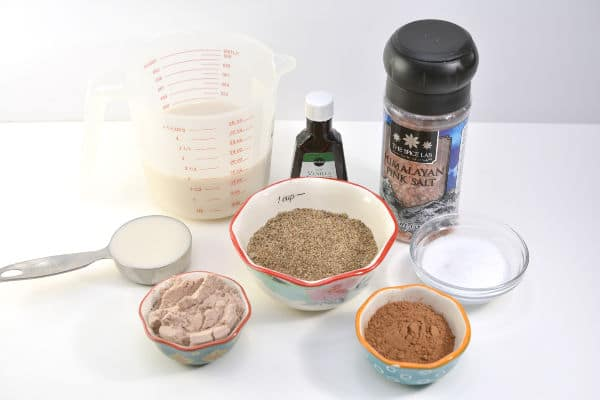 bowls and containers of Ground Chia Seeds, Unsweetened Vanilla Almond Milk, Low-Carb Chocolate Protein Powder, Unsweetened Cocoa Powder, Vanilla Extract, Salt, Erythritol