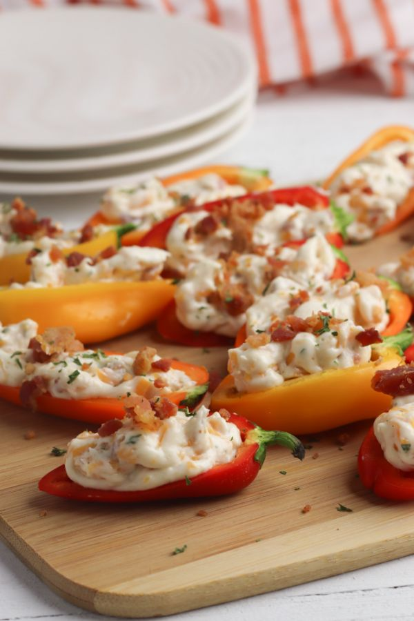 mini red and orange peppers stuffed with cream cheese, cheddar cheese, mayonnaise and bacon on a wooden cutting board on a white wood table with three stacked white plates and an orange and white striped linen in the background