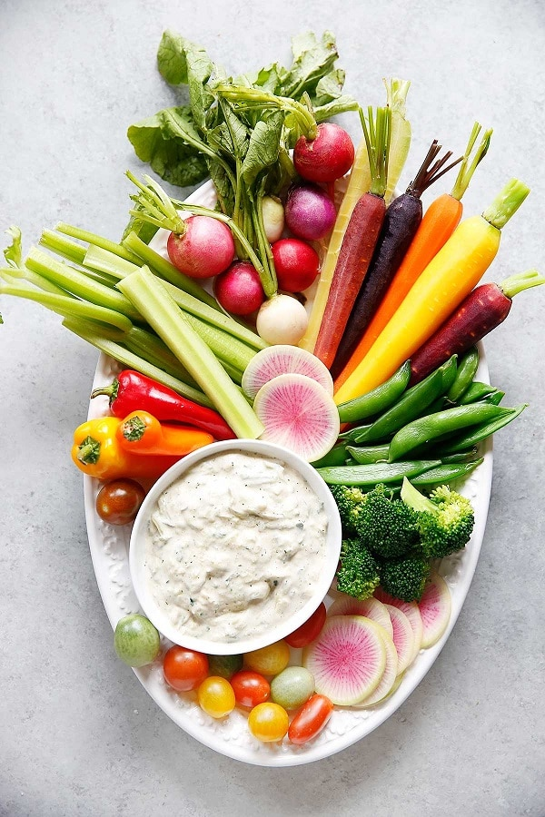 a platter with lots of vegetables and a bowl of dip on it on a light gray background