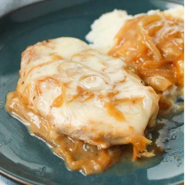 pork chops topped with sauce, cheese and onions on a plate next to mashed potatoes topped with onion and sauce