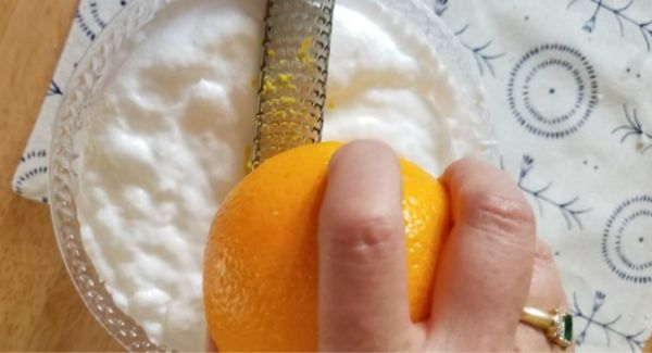 zesting orange over bowl of homemade kitchen cleaner on a blue and white cloth on a wood table