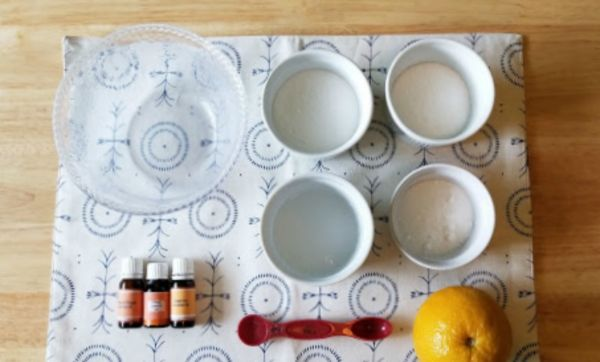 supplies needed to make homemade kitchen cleaner, like Baking Soda, Borax, Epsom Salts, Dish Soap, Peroxide, Essential Oils, Orange all on a blue and white cloth on a wood table