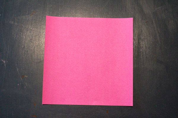pink origami paper on a dark brown background
