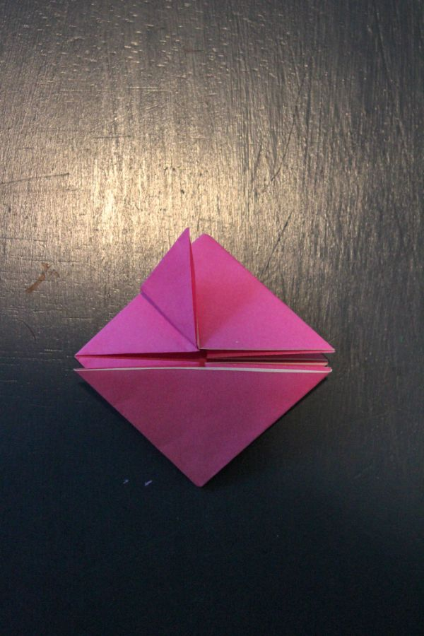 pink origami paper folded into two triangles on a dark brown background