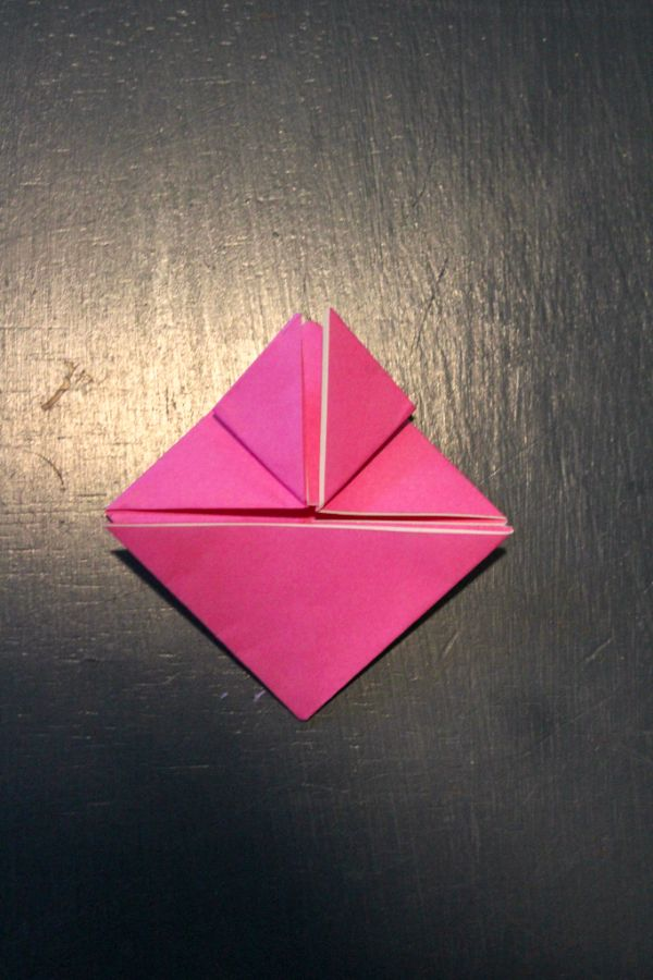 pink origami paper folded into triangles on a dark brown background