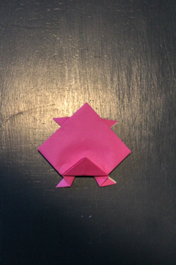 pink origami paper folded to look like it has legs on a dark brown background