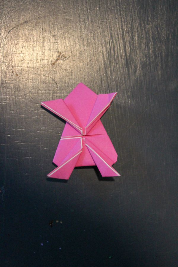 pink origami paper folded to look like a frog on a dark brown background