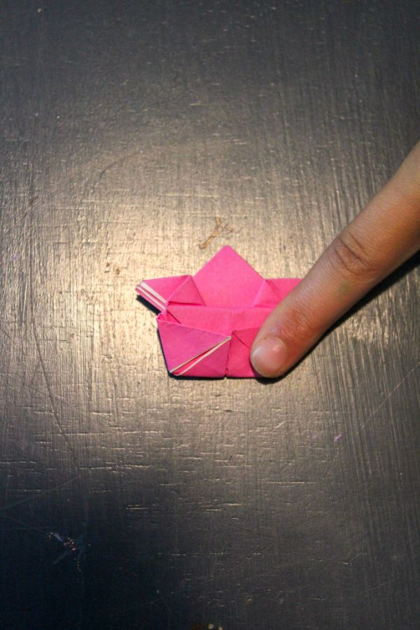 a hand touching pink origami paper folded to look like a frog on a dark brown background
