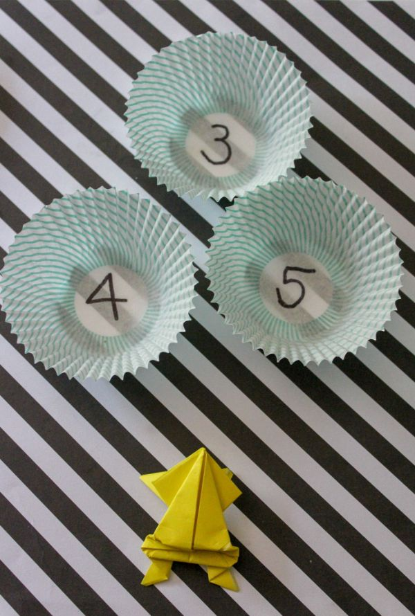 origami jumping frog and cupcake liners to jump into on a black and white striped background