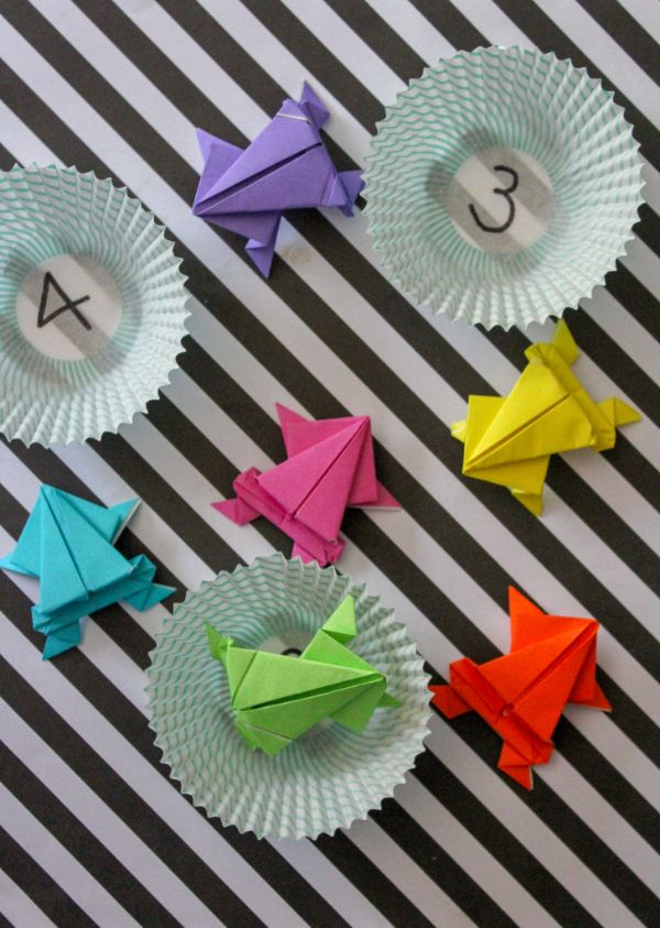 origami jumping frogs game in cupcake liners with numbers written in them and colored paper frogs, all on a black table