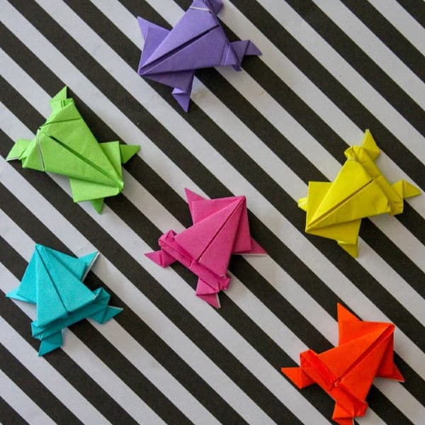 multi-colored origami frogs on a black and white striped background