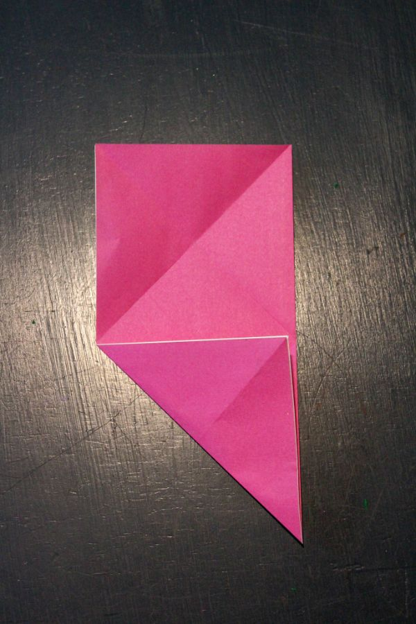 pink origami paper folded on a dark brown background