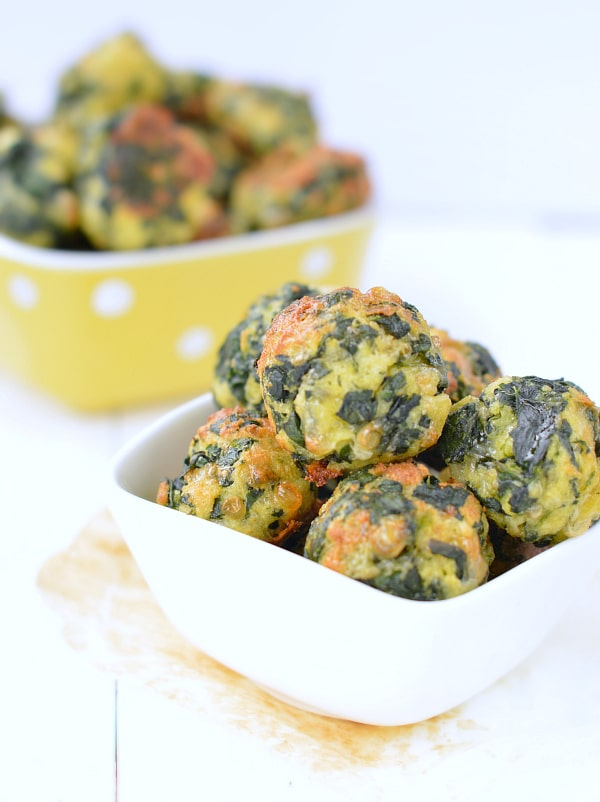 spinach ball appetizers in a white dish with more in the background in a yellow and white polka dot dish